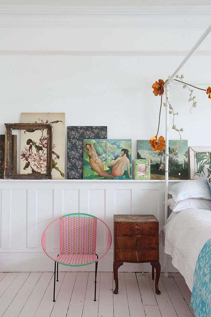 une chambre à coucher vintage avec soubassement en boiserie murale blanche avec espace rangement pour ranger des cadres et des tableaux