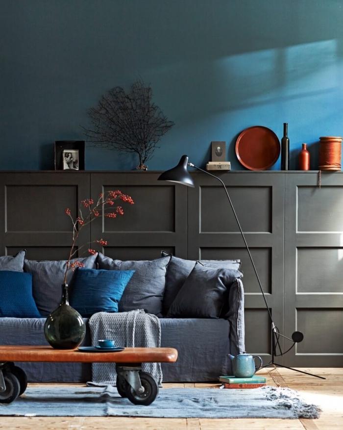 idée habillage mur intérieur bois pour sublimer le bas des murs, panneaux décoratifs à caissons couleur gris anthracite posés au mur du salon derrière le canapé munis avec un espace rangement dessus