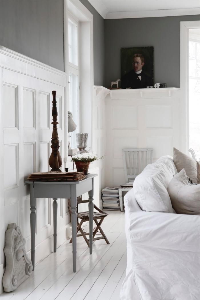 mur bicolore avec des panneaux décoratifs blancs posés en soubassement qui s'harmonisent avec les planches de bois blanc du sol