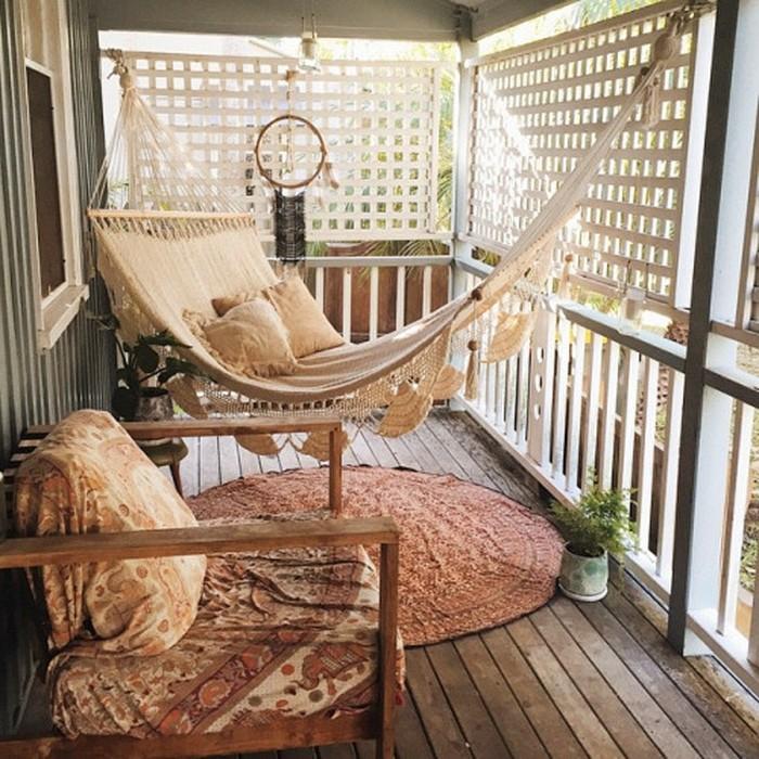 idée de hamac style boheme chic sur une terrasse en bois composite, attrape reve decoratif, fauteuil en bois, brise vue originale, aménagement petit balcon