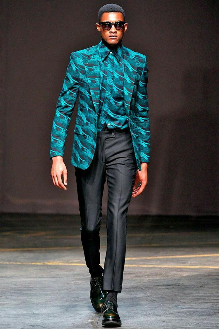 modèle africainportant une tenue africaine pour homme, pantalon noir et chemise turquoise, veste motifs ethniques, lunettes de soleil