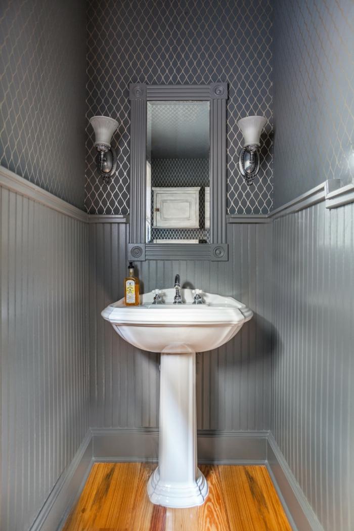 toilettes en gris, vasque pied blanche, deux appliques et miroir encadré, papier peint mural géométrique, sol en bois