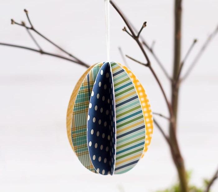 decoration branche de bois avec un oeuf de papier cartonné 3d à divers motifs, exemple bricolage de paques