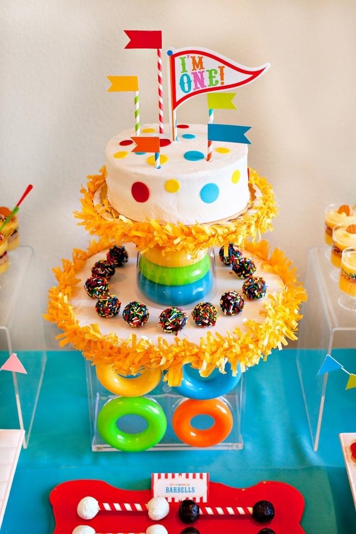 un gâteau enfant sur le theme anniversaire cirque, gâteau d'anniversaire au glaçage lisse blanc orné de petits ronds en pâte à sucre