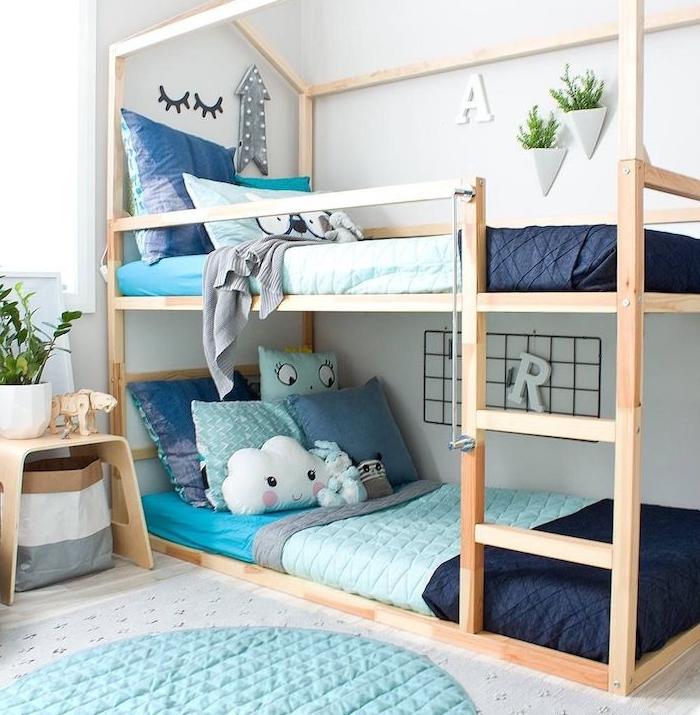 lits superposées en bois style scandinave pour gain de place dans la chambre montessori, linge de lit bleu, table de nuit bois, tapis rond bleu