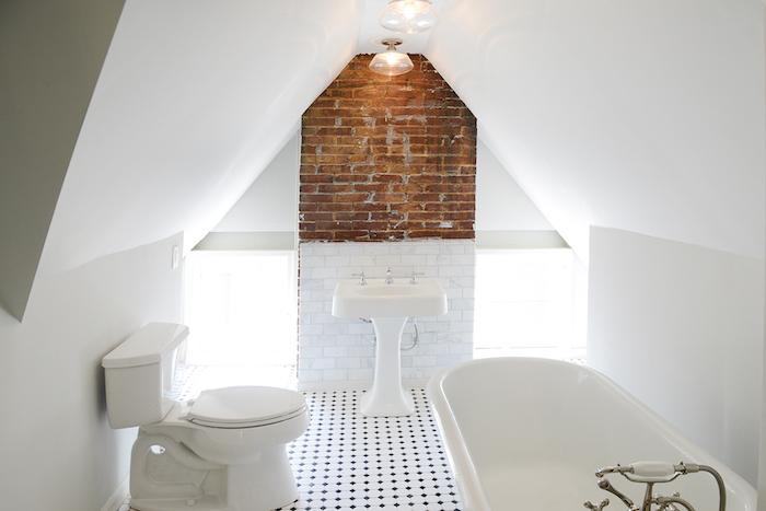 salle de bain mansardée originale avec accent mur de briques, lavabo et wc blanc sur carrelage sol noir et blanc