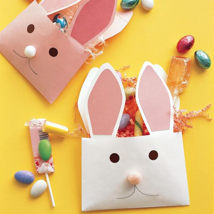 enveloppe de papier à motif lapin au nez de pompon et oreilles de papier, des yeux points noirs, rangement friandises et chocolats de paques