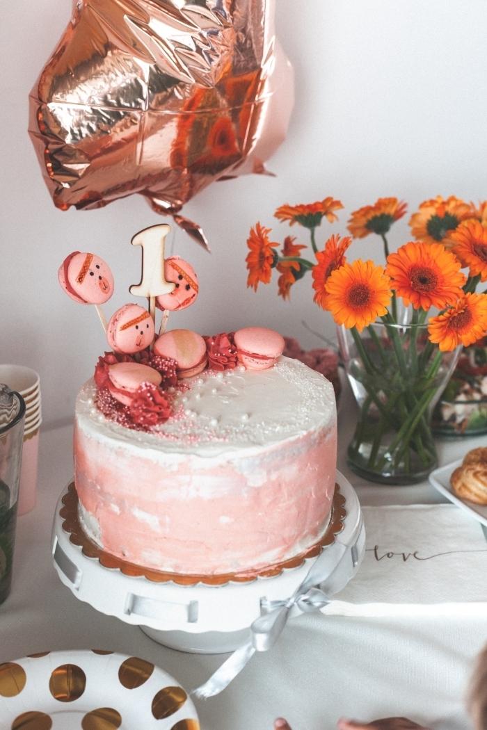 jolie décoration de gateau anniversaire fille avec des macarons roses et des perles en sucre, un gâteau d'anniversaire 1 an au glaçage rose et blanc