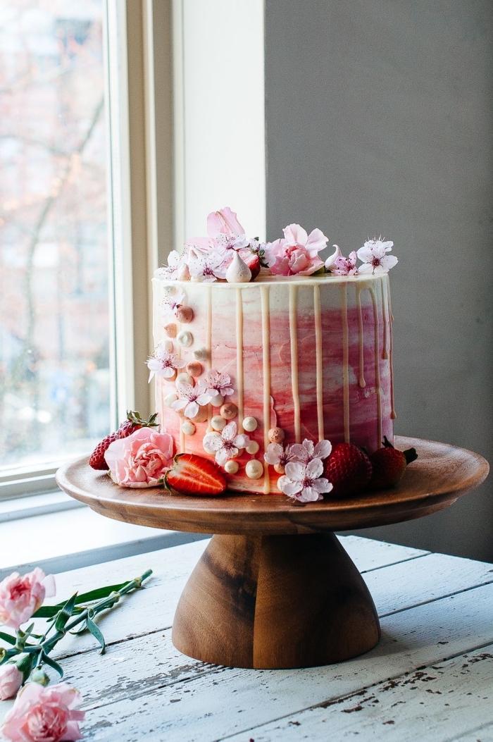 gateau anniversaire simple et beau au glaçage coulant de chocolat blanc avec une jolie décoration de fleurs de cerise et de meringues
