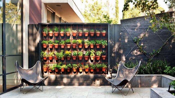 jardiniere haute avec des pots d'herbes aromatiques posés sur une grille métalliques, un adorable patio avec mur végétal