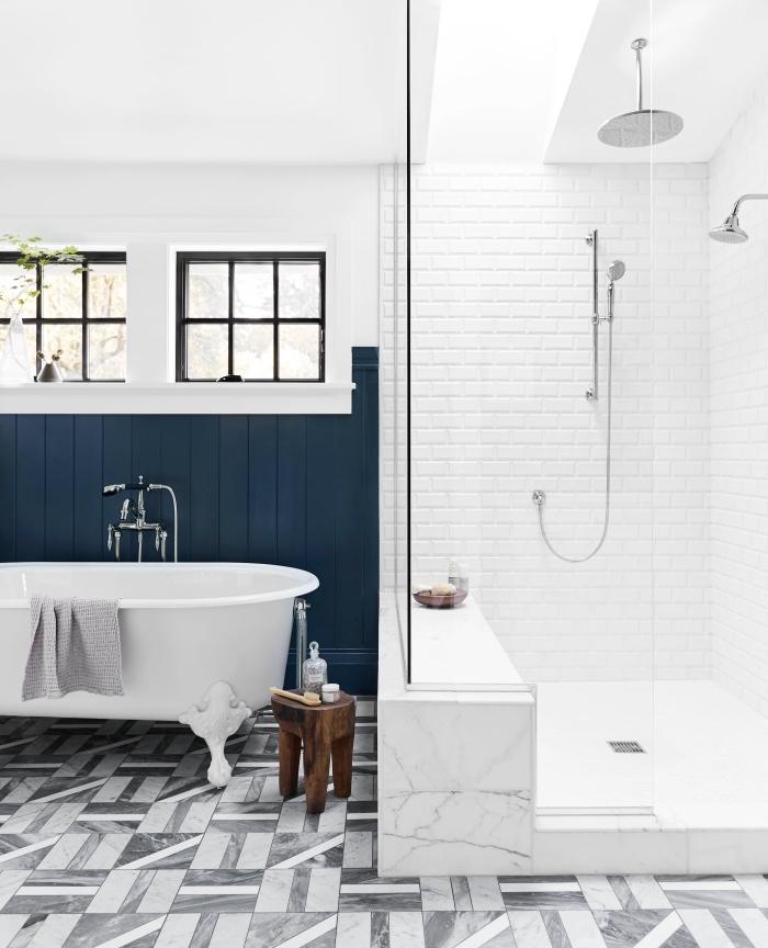 une salle de bains élégante avec cabine de douche et baignoire mise en valeur par un soubassement de lattes peint en bleu foncé qui joue fait office de crédence baignoire, de quelle couleur peindre du lambris dans la salle de bains