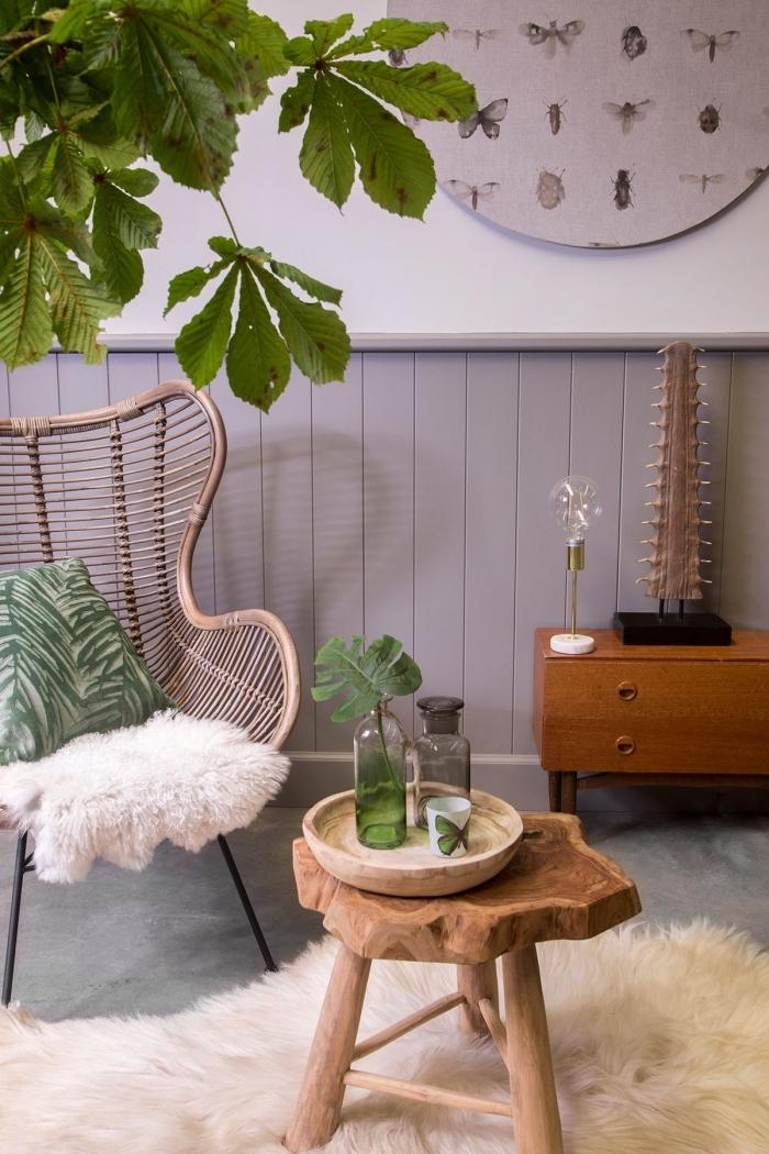 soubassement en bois peint en couleur mauve qui habille le mur d'un salon de style vintage bohème décoré avec des touches de bois et de vert