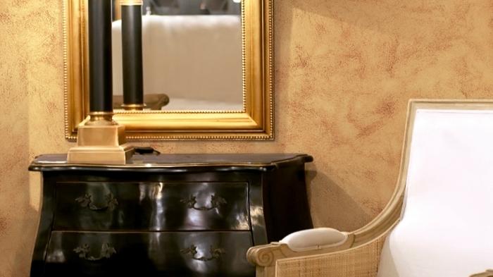 quel revêtement mural pour un salon, déco de pièce aux murs sablés de nuance dorée avec meubles or et noir