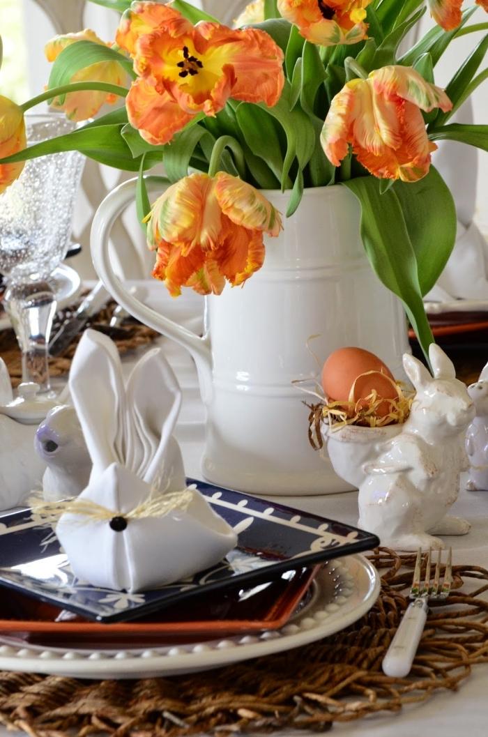 décoration de table de pâques de tulipes, de porte-oeufs lapins en céramique, serviette en forme de lapin paques arrangé dans une belle assiette noire et blanc