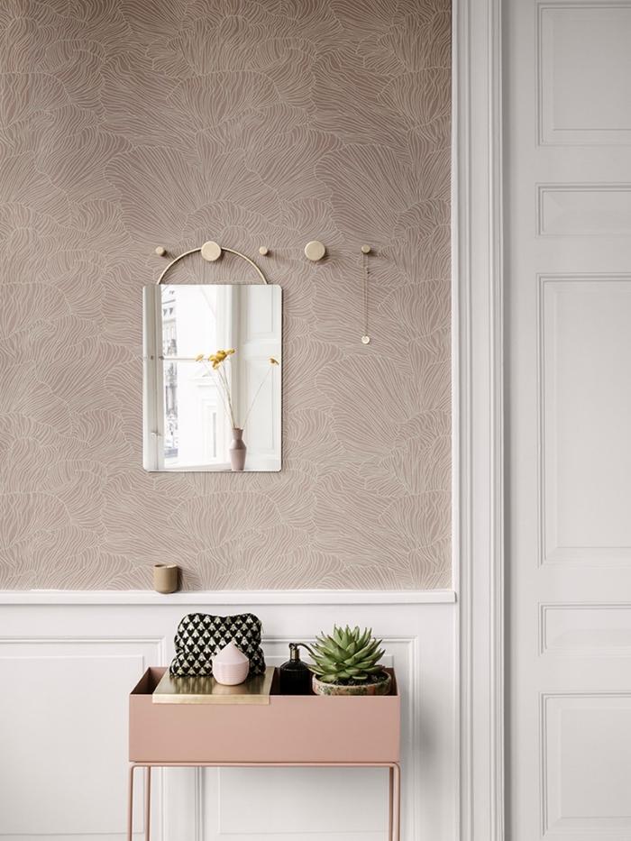 la boiserie murale blanche met en valeur la jolie couleur rose cendré du papier peint intissé posé dans la partie haute du mur