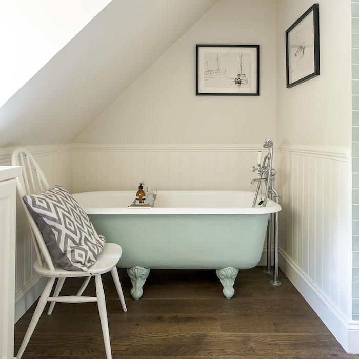 aménager une petite salle de bain avec sol de parquet marron, chaise blanche, baignoire vert clair, murs blancs et soubassement bois blanc