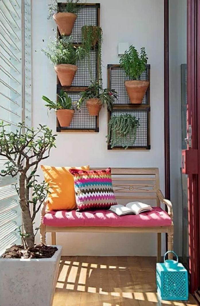 deco balcon simple en banc de bois décoré de coussins colorés, revêtement sol bois, mur végétal de pots fleuris