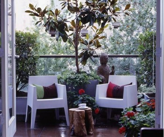 aménagement de balcon étroit, chaises blanches décorées de coussins colorés et petite table basse en tronc d arbre, statuette de bouddha, plantes vertes et plantes fleuries zen