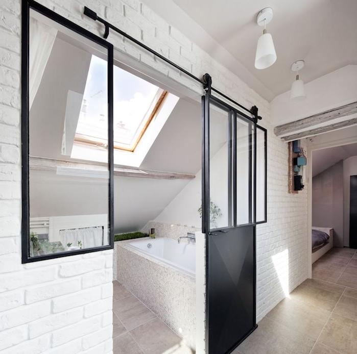 mini salle de bain 2m2 sous pente, porte galandage noire, murs blancs et carrelage gris clair, fenêtre de toit