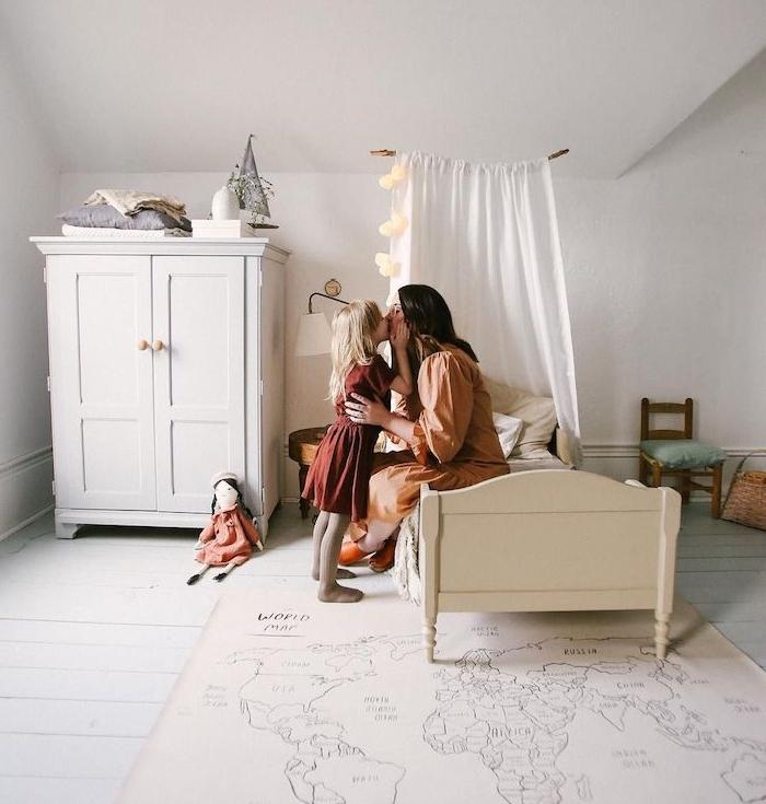 amenagement chambre enfant sous pente en blanc avec lit bas blanc, armoire basses, petite chaise, tapis mappemonde sur parquet blanchi à la scandinave