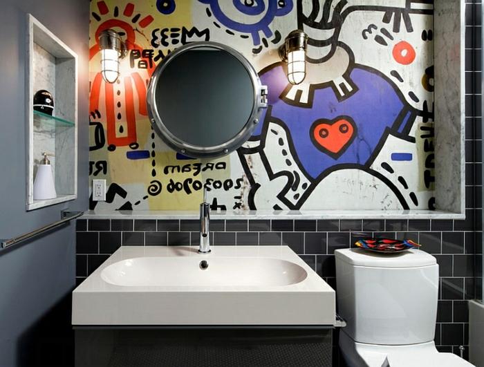 carrelage toilette métro noir, peinture murale originale avec dessins colorés, miroir rond, vasque à poser blanche, mur gris, deux appliques industrielles