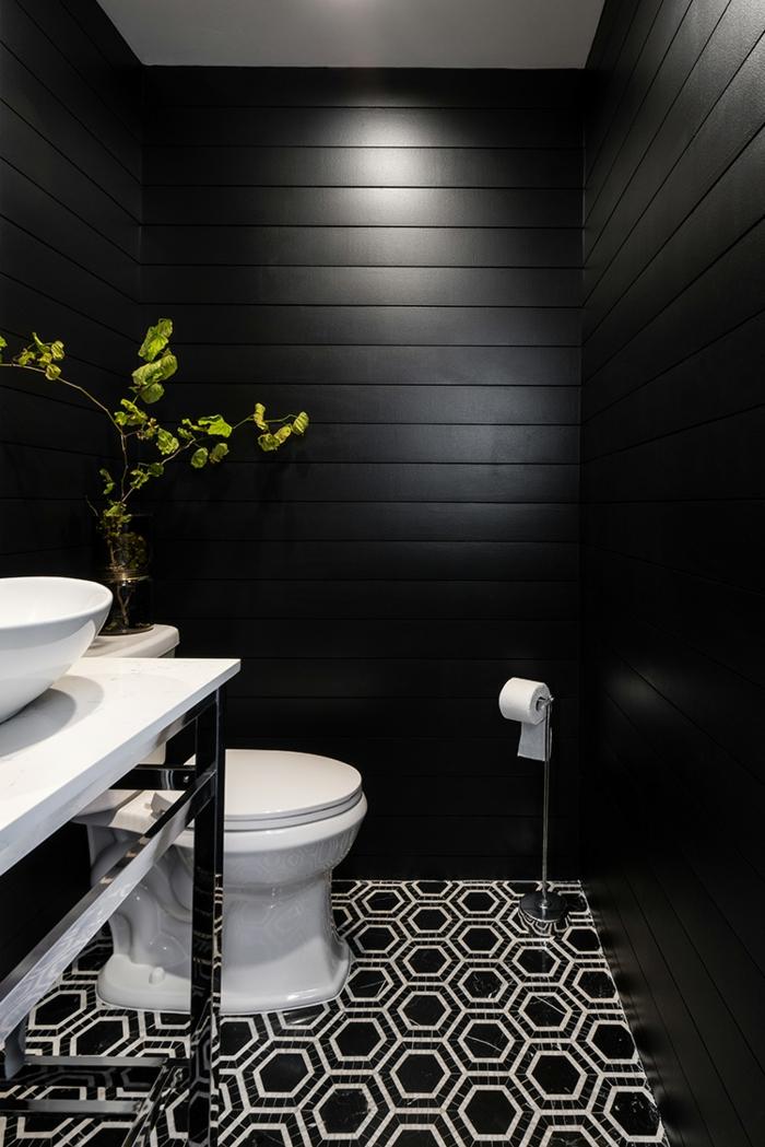 deco toilettes originales, sol aux motifs géométriques, plante décorative, vasque à poser blanche, lambris mural noir