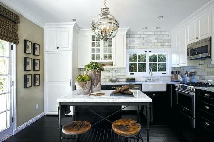 îlot de cuisine noir et blanc, tabourets en bois et métal, sol planches noires, carreaux blancs, chandelier