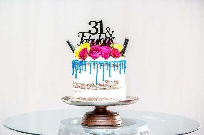 un gâteau d'anniversaire au glaçage coulant bleu décoré d'un cake topper personnalisé et de fleurs
