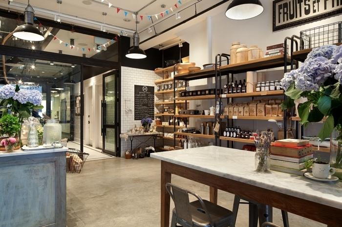 grande cuisine loft, table bois et blanche, chaises tolix grises, hydrangeas lilas, lampes usine, étagère métal et bois