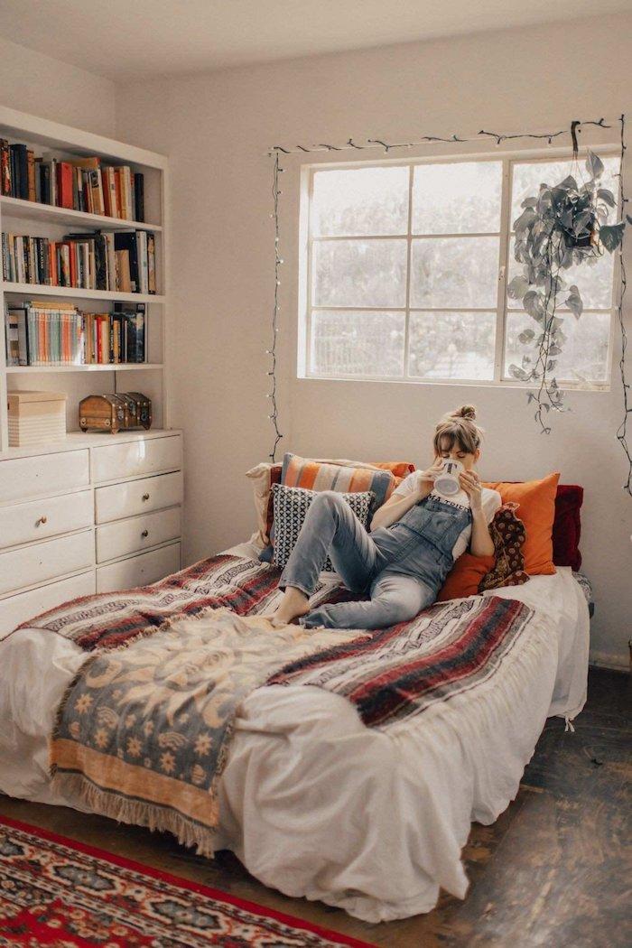 Boire thé au lit, fille en salopette jean, étagère avec livres, linge lit bohème, tapis motif oriental, plante verte pendant