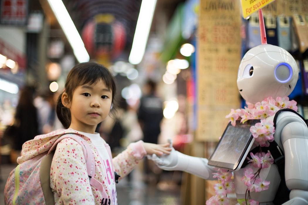 Belle fille voit un robot qui lui semble mignon, robot apprend à jouer à Jenga, robot avec guirlande de fleurs