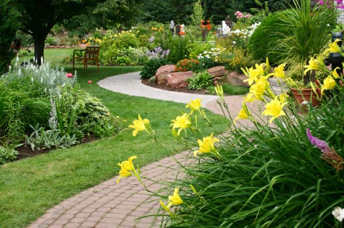 massif fleures, allée de jardin, petit ilot de pierres dans un jardin paysager, lys jaunes
