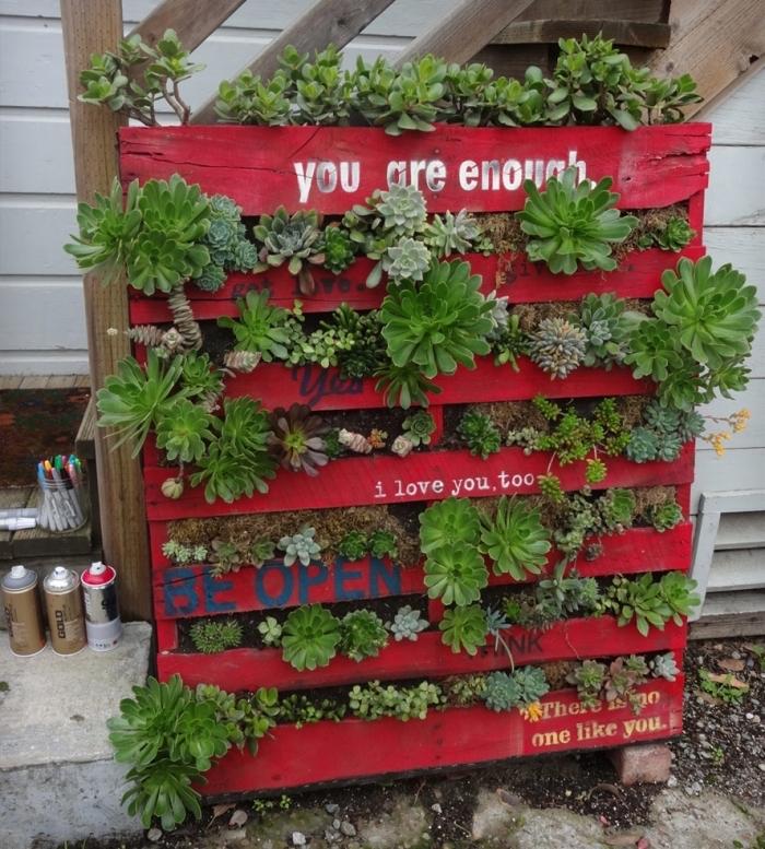 une jardiniere haute de plantes succulentes en palette recyclée repeinte en rouge avec citations inspirantes
