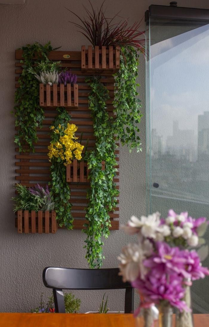une structure murale avec des lattes en bois et des bacs à planter pour créer un jardin vertical gain de place sur le balcon