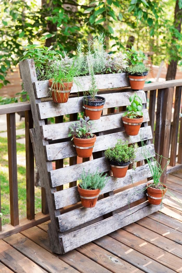 un jardin vertical en palette recyclée sur laquelle on a fixé des pots de plantes aromatiques