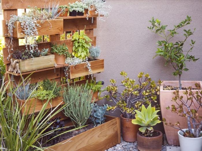 une jardiniere haute en bois avec plusieurs bacs à planter à niveaux différents pour cultiver des fleurs et des aromatiques à la verticale