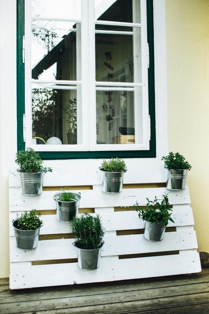 des pots en zinc fixés sur une palette recyclée repeinte en blanc, aménager un jardin en hauteur grâce à une palette de bois