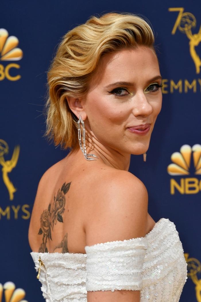 jeune star en robe blanche, tatouage au dos rose, cheveux au carré court, trait d'eyeliner