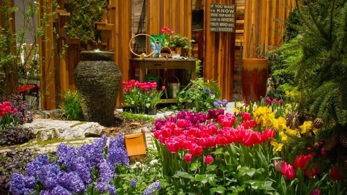 massif fleurs, jacinthes et tulipes, grand vase décoratif, arbustes et fleurs arrangés ensemble