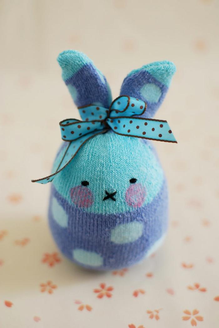 lapin bleu avec ruban pointillé, yeux et bouche brodés, joues roses dessinées avec un marqueur