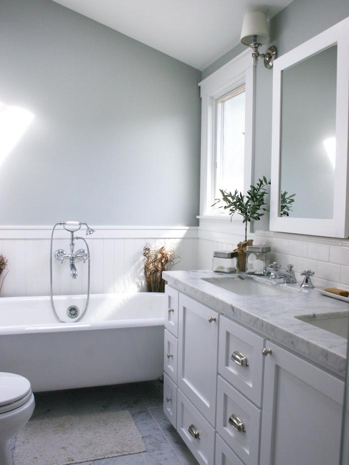 une salle de bains avec du lambris blanc en soubassement associé à une peinture murale gris perle et à du carrelage blanc métro