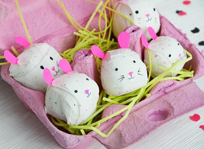 decoration de paque à faire soi meme, carton à oeufs peint rose, herbe artificielle, lapins papier mâché