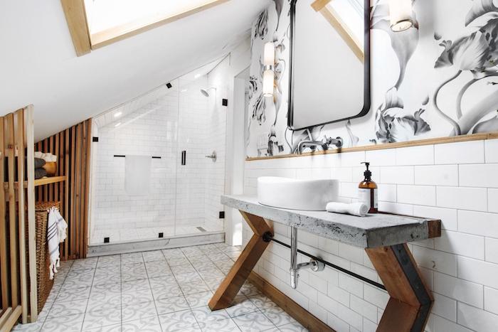 agencement salle de bain intéressant avec une douche sous pente et carrelage blanc, meuble vasque avec pieds de bois et plan de travail éton, accents boisés et pan de mur papier peint salle de bain