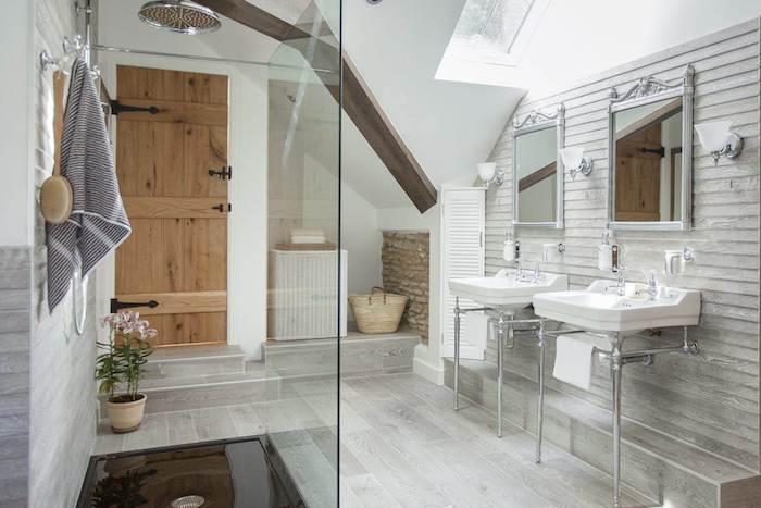 porte galandage rustique dans une salle de bain, lavabo console ancien, miroirs vintage, parquet gris clair, douche vitrée