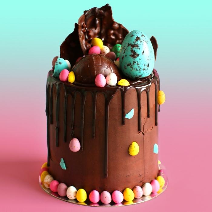 gâteau layer cake au chocolat dégoulinant au glaçage de crème beurre en chocolat garni d'oeufs de pâques en chocolat, gateau au chocolat au lait à servir en dessert de pâques