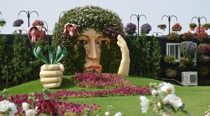 statue géante qui tient un bouquet de tulipes, pelouse verte, massif de fleurs lilas