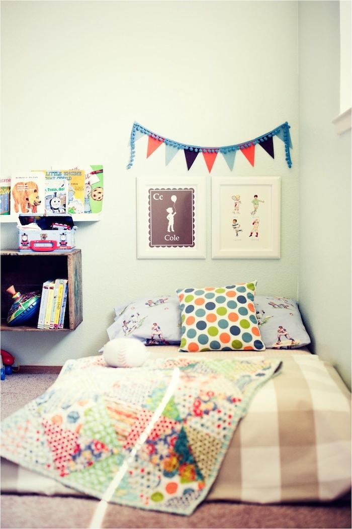 lit au sol décoré de couverture et coussins colorés, tapis gris, murs blancs, table de nuit cagette bois recyclée, tete de lit en cadres décoratifs, bibliothèque minimaliste enfant