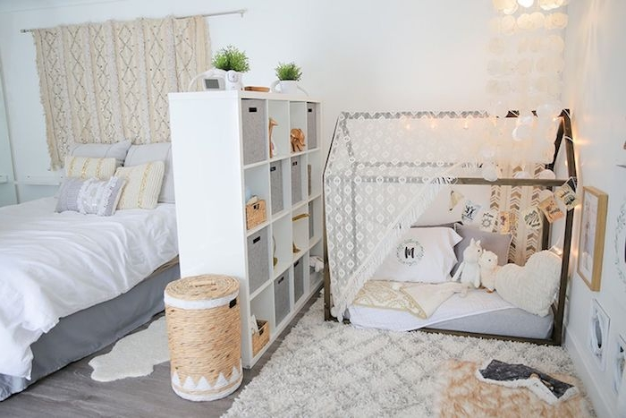 amrenagement chambre adulte avec un espace montessori séparé d une étagère, lit cabane au sol décoré de jouets et coussins, lit avec linge gris et blanc
