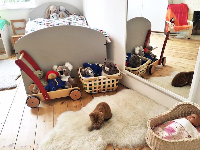 lit gris bas avec couverture colorée, miroir mural, tapis moeulleux avec chat dessus, parquet bois clair, paniers à jouets