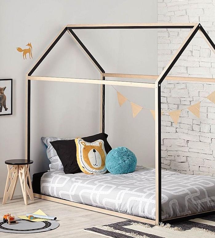 lit cabane pour enfant en bois et noir, mur imitation briques blanches, parquet bois clair, table de nuit tabouret, mur blanc, tapis beige et noir